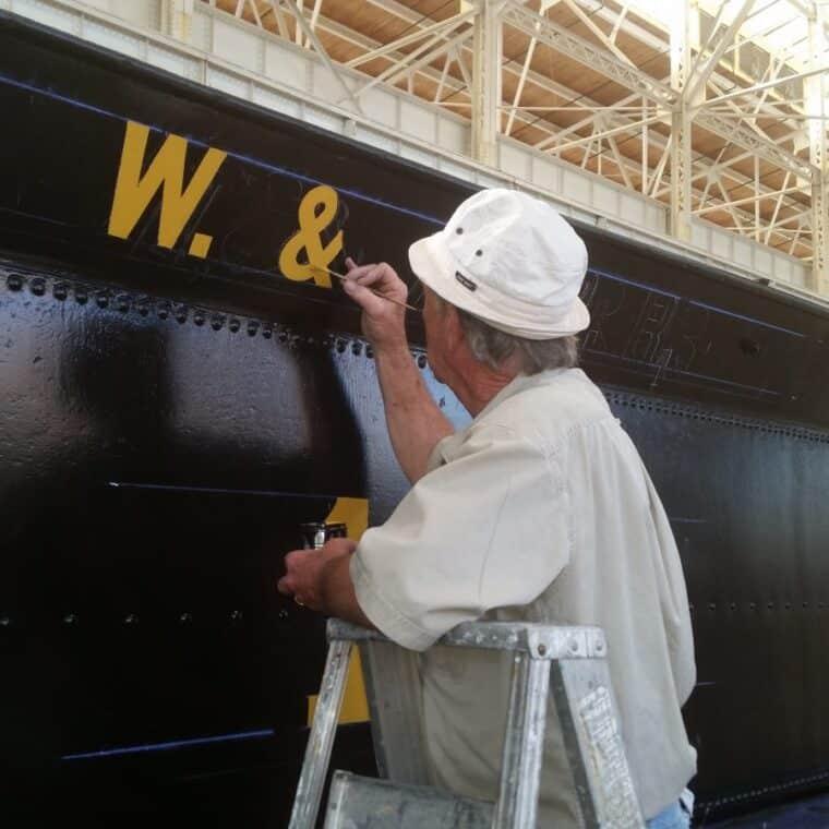 man paints the locomotive