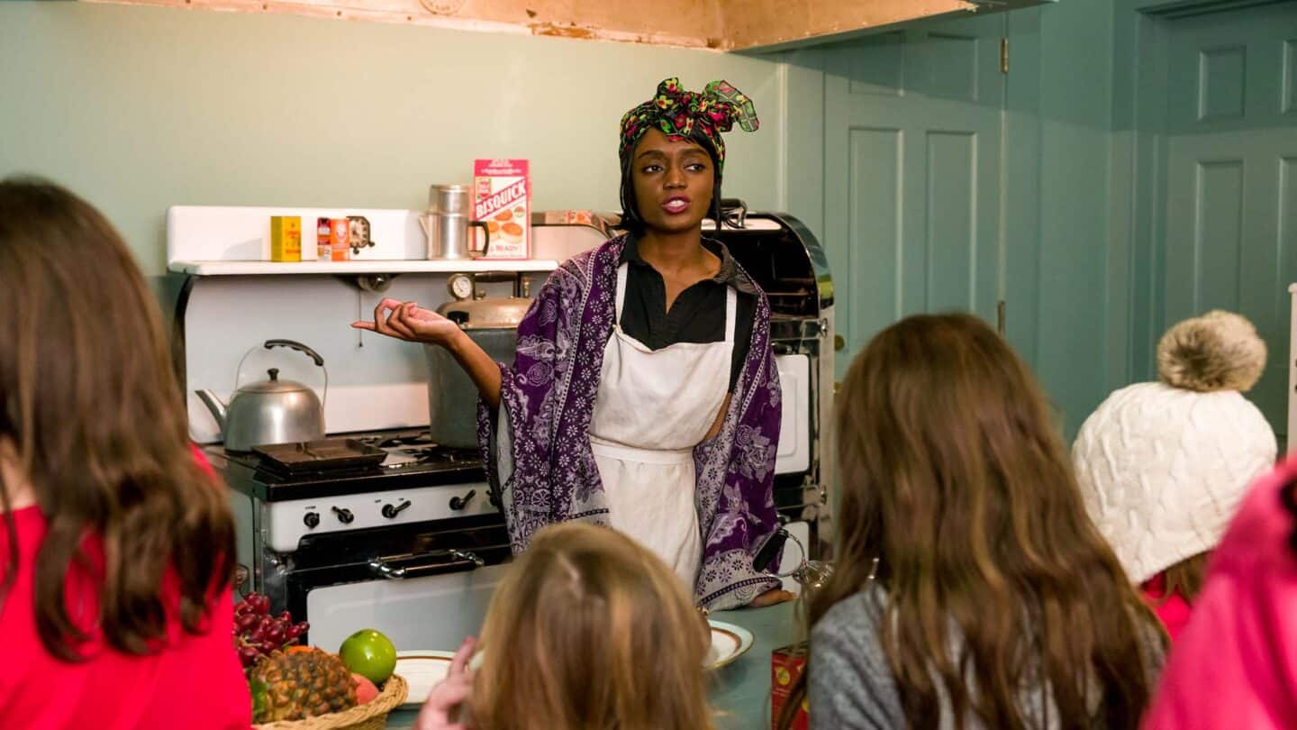 black woman in kitchen performing during Candlelight Nights
