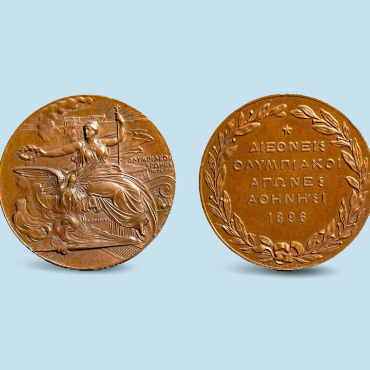 Two bronze coins with a character on side and wreath and writing on the opposite