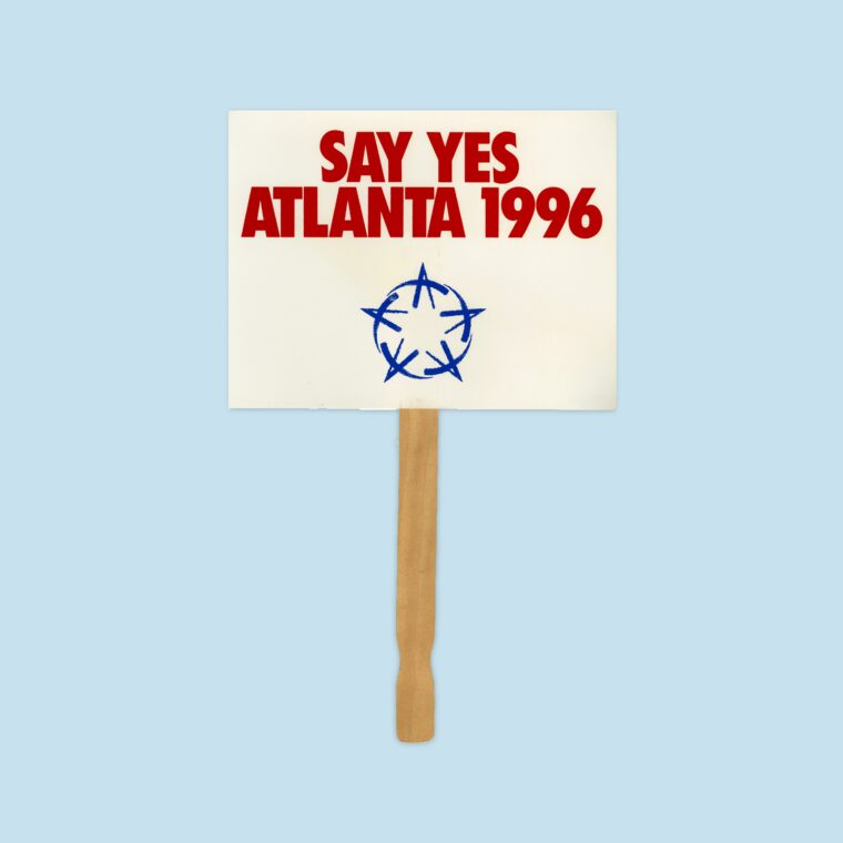White handheld sign with red text that says Say Yes Atlanta 1996 and blue Olympic icon