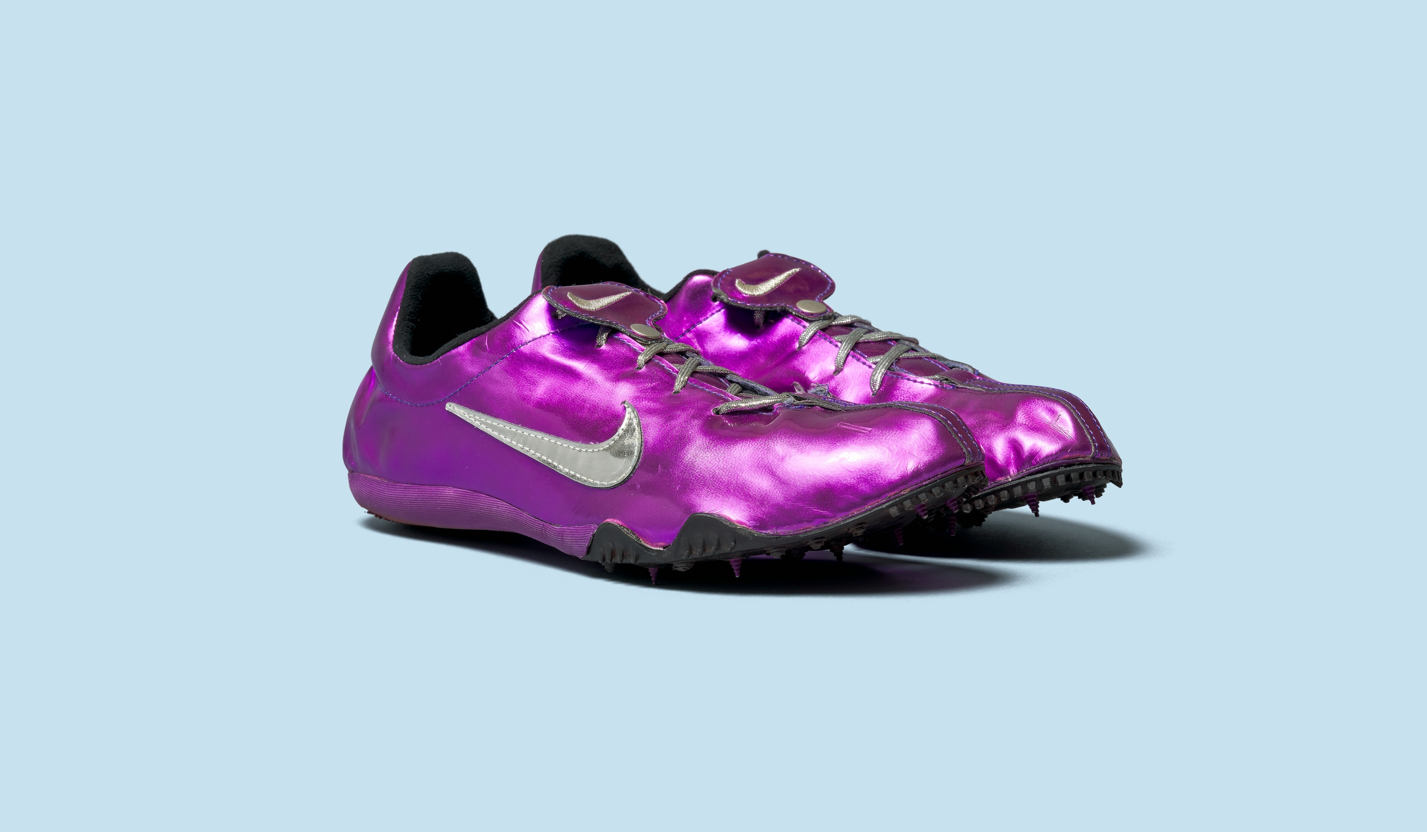 Purple track shoes on blue background