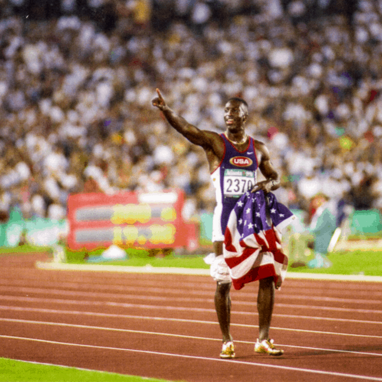 Image of Black track runner holding American flag and pointing while standing on track