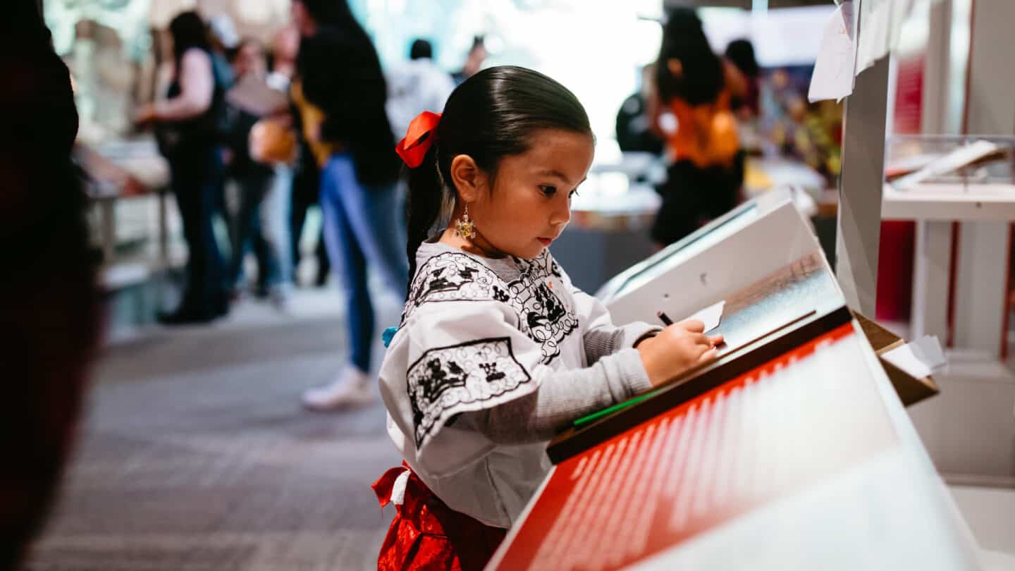 young girl writing at Day of the Dead Event