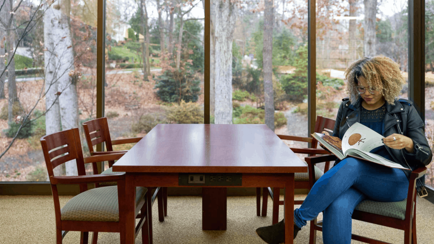 woman sitting at table reading, while at Kenan research center