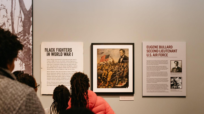 guests gazing at Eugene Bullard display, and Black fighters display