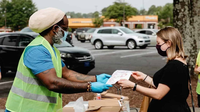 volunteers help out at Mi Gente Mural Drive by