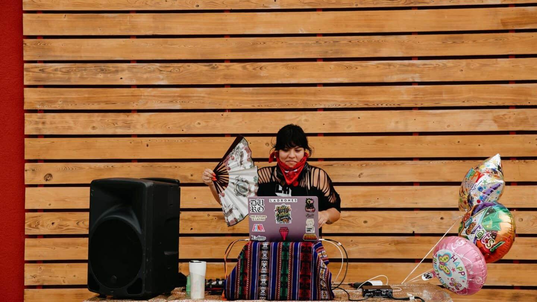 DJ that is a woman, holds a fan