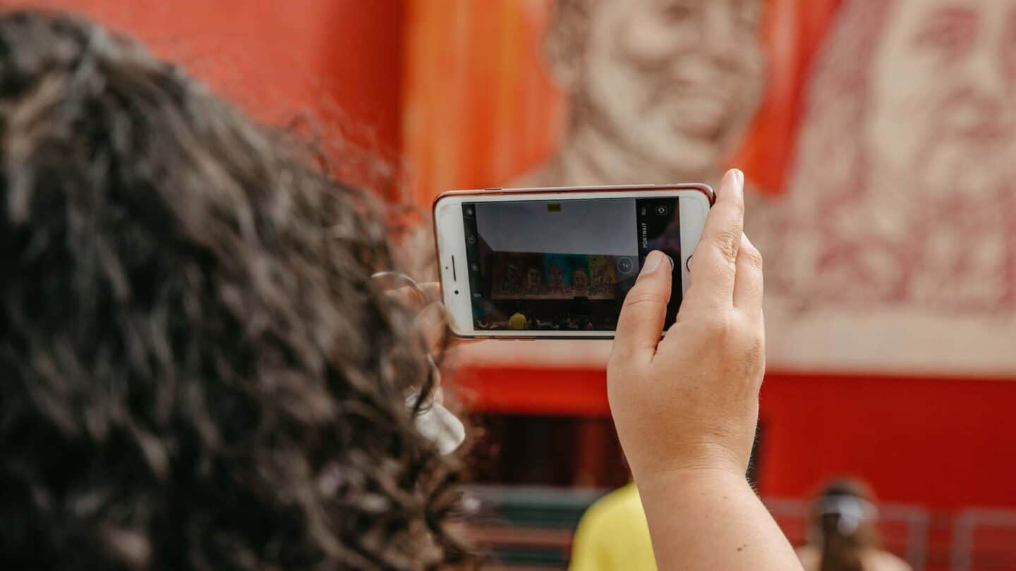 woman with curly hair captures picture of mural