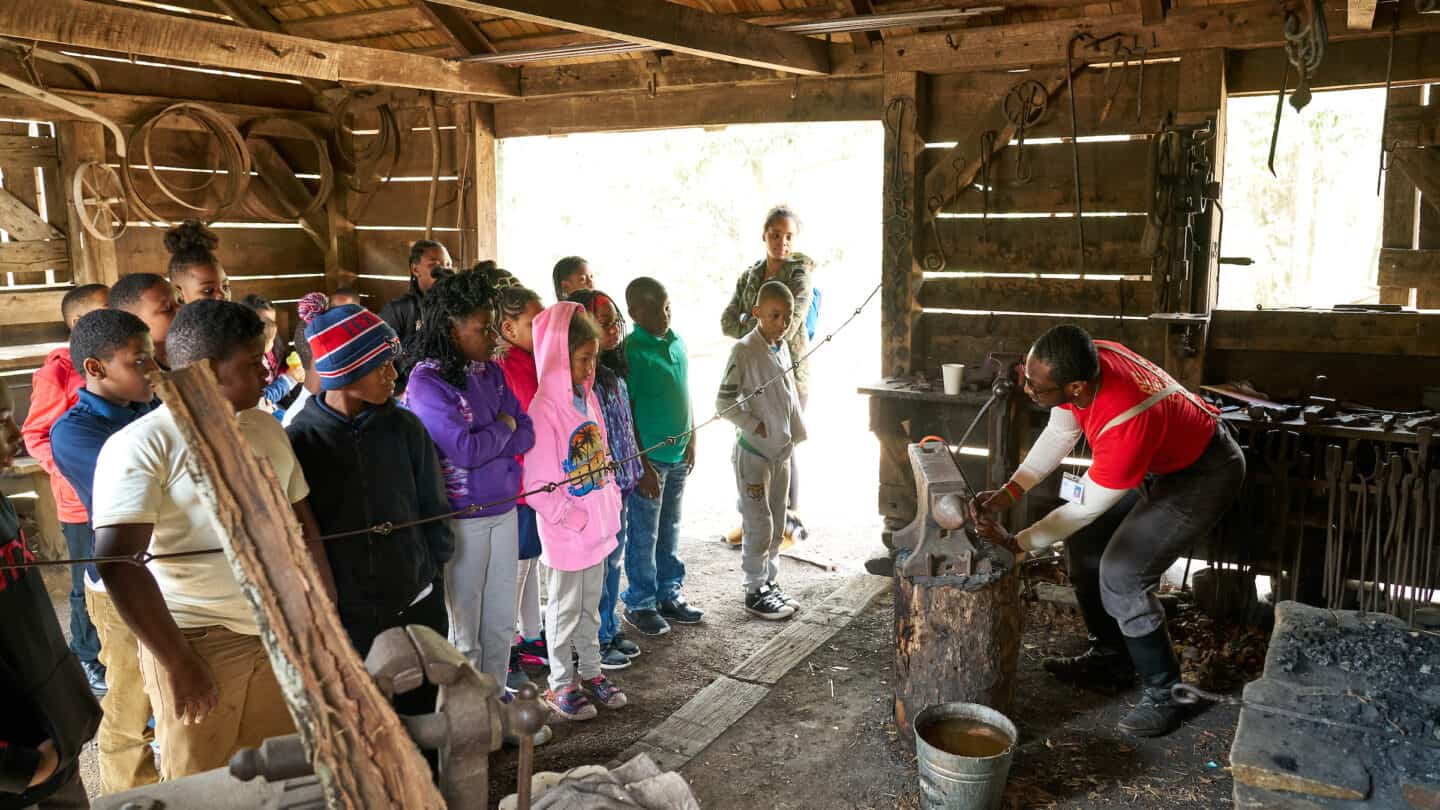 kids learning from a museum volunteer