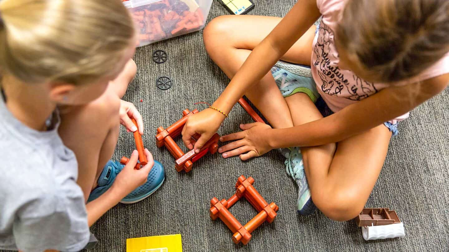 two girls at summer camp play on floor