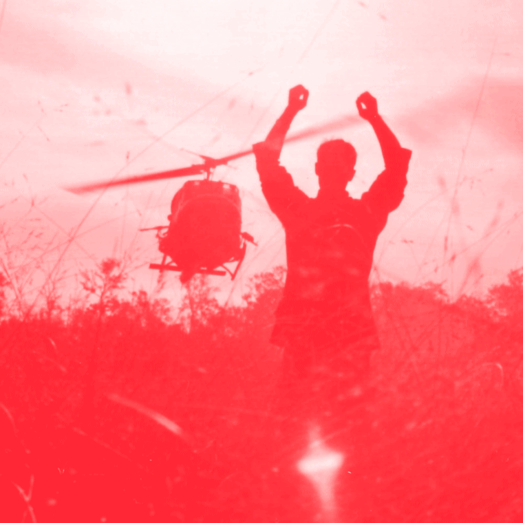 helicopter and man's hands raised in the air