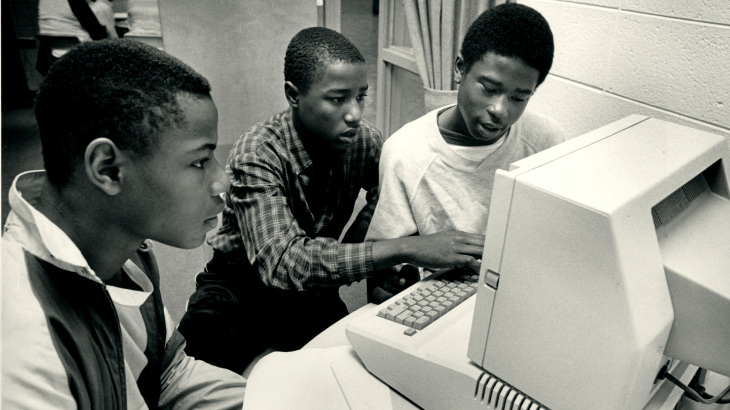 three young boys sitting around a computer