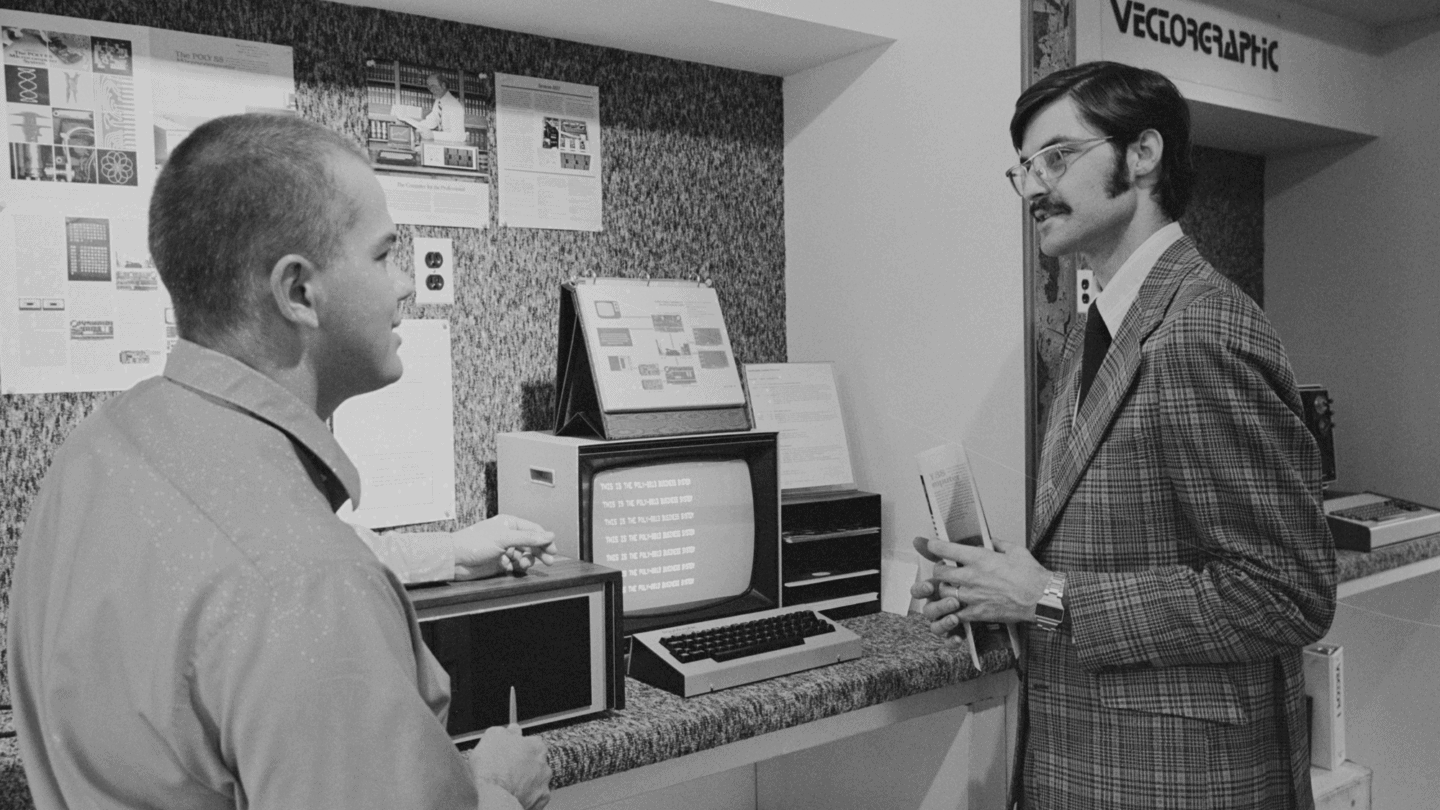 Two Men Talking in front of computer