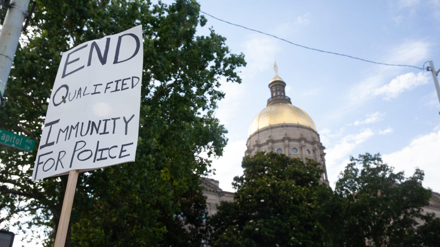 sign saying End qualified immunity for police