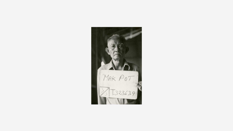 man holds sign at refugee camp