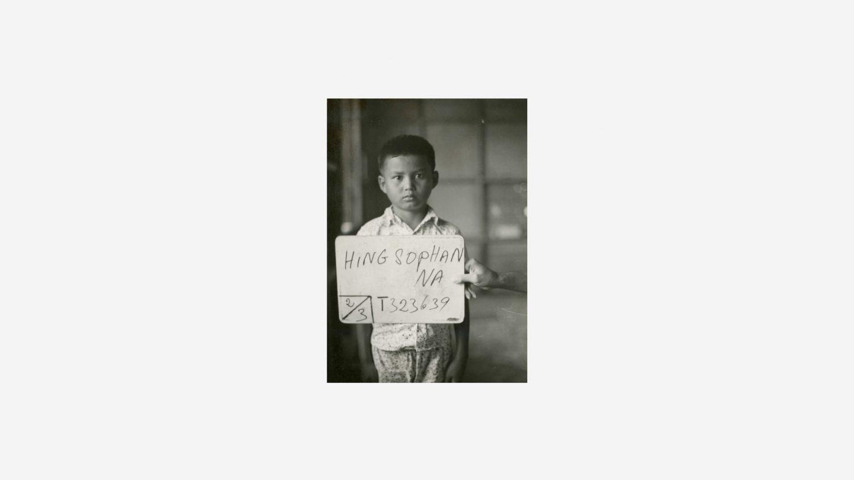 little boy holds sign at refugee camp