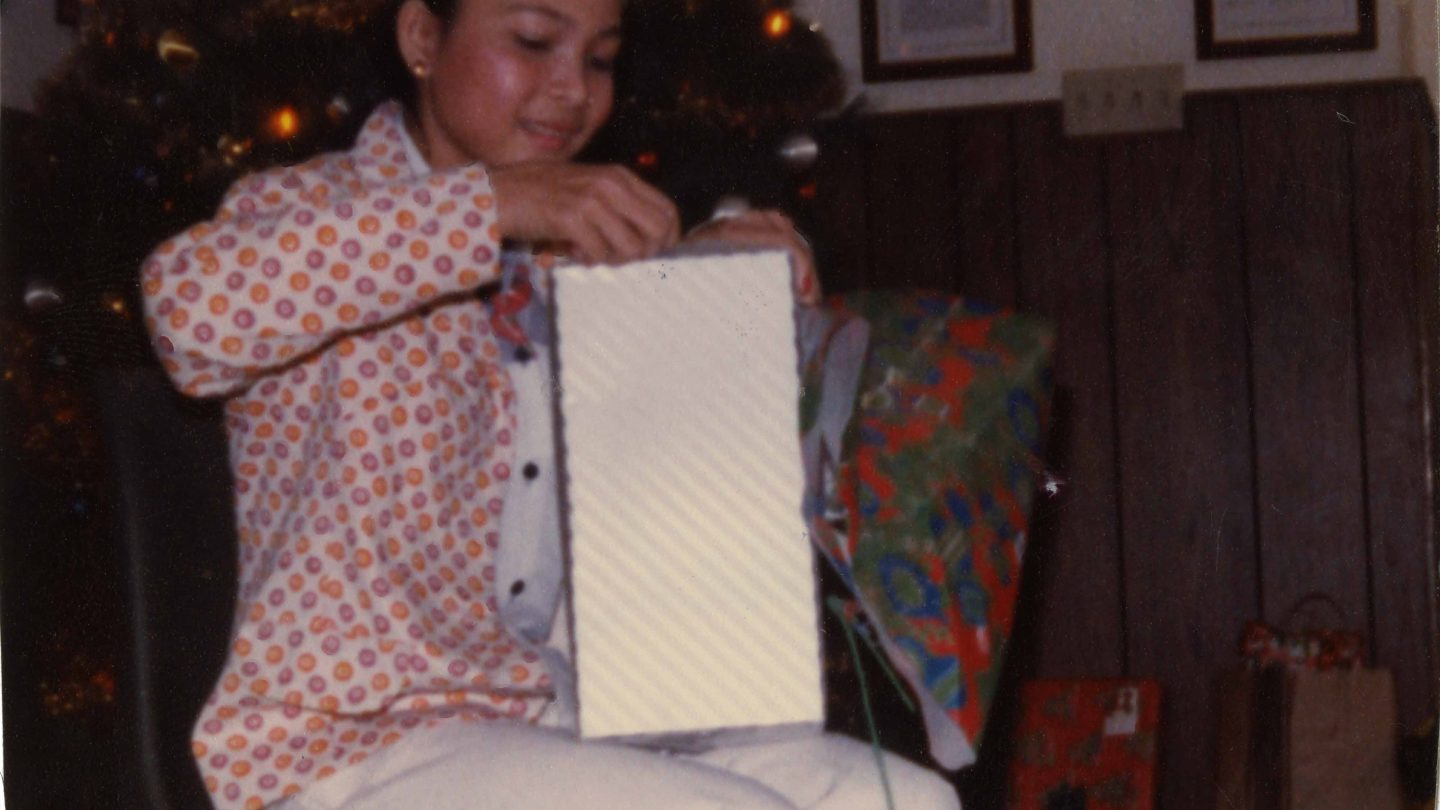 young refugee girl opening a Christmas present