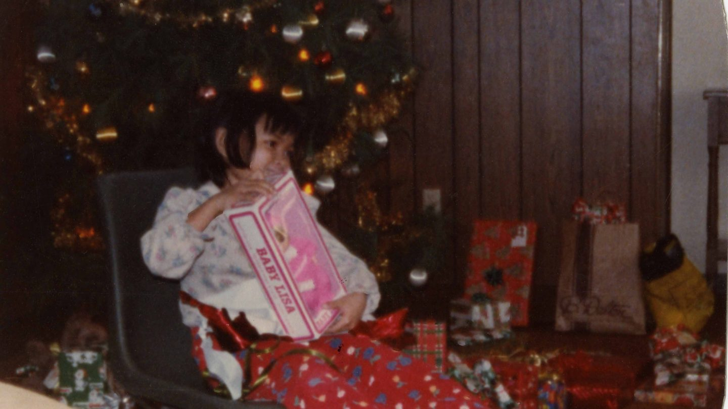 girl opening a baby Lisa doll under the Christmas tree