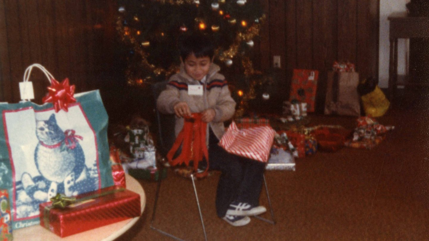 boy opening a Christmas present while sitting down