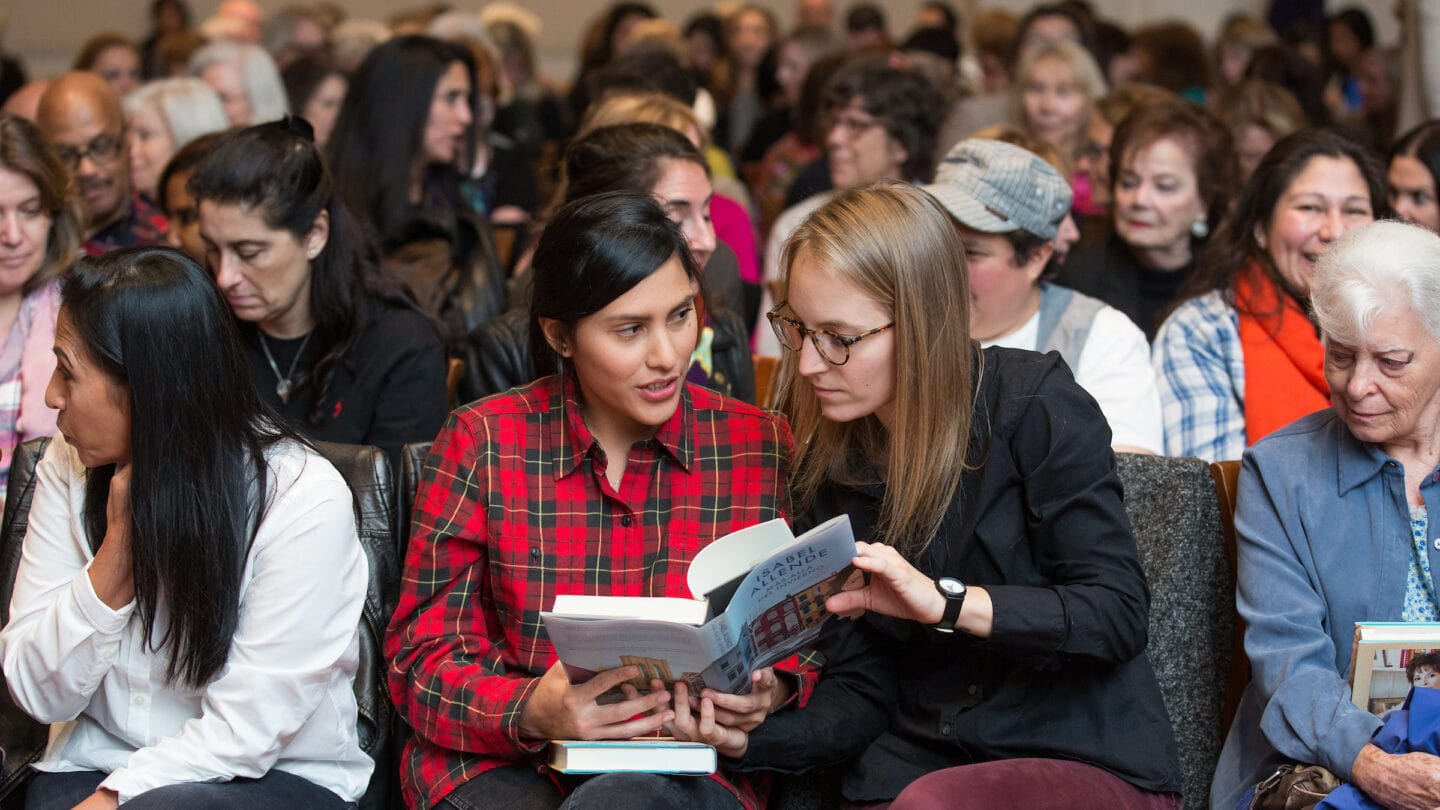 Two women sitting in a crowd looking at a book